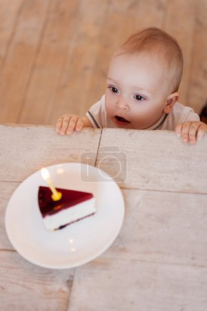 Baby looking at cake