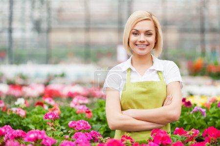 Foto de Mi trabajo es mi pasión. Hermosa joven en delantal manteniendo los brazos cruzados y sonriendo mientras está de pie en un invernadero - Imagen libre de derechos