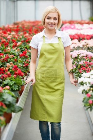 Photo for Passionated about her job. Beautiful blond hair woman standing in flower bed and smiling - Royalty Free Image