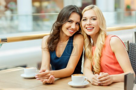 Photo for Two friends in cafe. Two young female friends sitting in cafe and looking at camera - Royalty Free Image