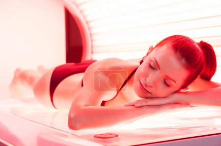 Sunbathing on tanning bed. Beautiful young woman l...