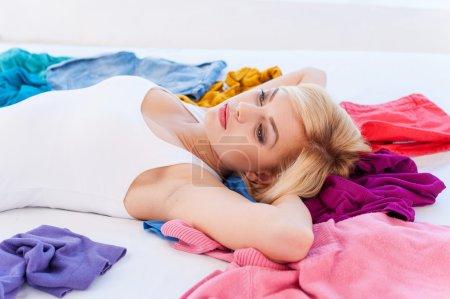 Photo pour Je n'ai rien à porter ! Jeune femme aux cheveux blonds déprimée allongée sur le lit avec des vêtements tout autour d'elle et regardant ailleurs - image libre de droit