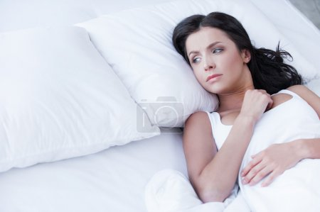 Photo for Loneliness. Depressed young woman lying on the bed and looking on empty pillow - Royalty Free Image