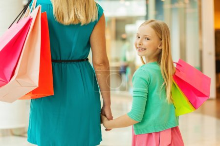 Mother and daughter holding shopping bags
