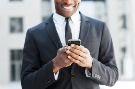 African man in formal wear holding mobile phone