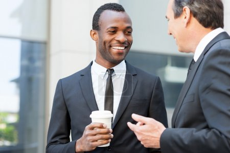 Photo for Talking during coffee break. Two cheerful business men talking while one of them holding coffee cup - Royalty Free Image