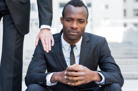 Photo pour Il lui faut un soutien amical. Frustré jeune homme africain en tenue de cérémonie assis sur l'escalier tandis que quelqu'un touche son épaule avec la main - image libre de droit