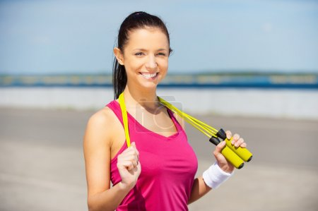 Woman in sports clothing holding jumping rope