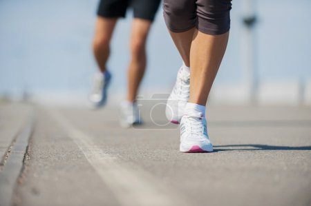 Photo for People running.  Close-up image of woman and man running along the running track - Royalty Free Image