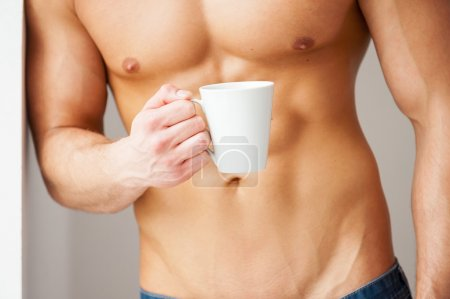 Muscular man holding cup of coffee