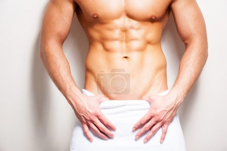 Photo pour Corps masculin parfait. Gros plan d'un jeune homme torse nu recouvert d'une serviette sur fond blanc - image libre de droit