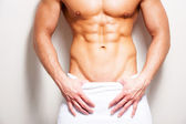 Shirtless man covered with towel