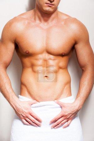 Photo pour Corps masculin parfait. Gros plan d'un jeune homme torse nu recouvert d'une serviette sur fond - image libre de droit