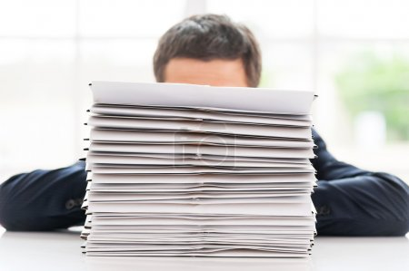 Businessman hiding behind stack of documents