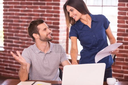 Man sitting at his working place and woman standing