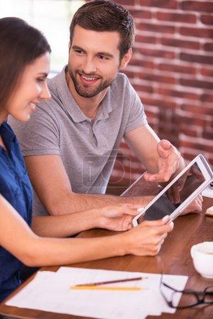 Foto de Discutiendo un nuevo proyecto de negocio. Vista lateral de alegre joven hombre y mujer sentados a la mesa y hablando mientras el hombre señala la tableta digital y sonriendo - Imagen libre de derechos