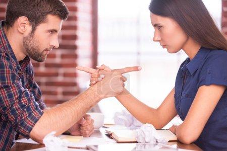 Photo pour Se blâmer mutuellement. Image latérale de l'homme et de la femme en colère assis face à face à la table du bureau et se montrant du doigt - image libre de droit