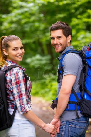 Photo pour Couple voyageant avec des sacs à dos. Heureux jeune couple aimant portant des sacs à dos et regardant par-dessus l'épaule avec le sourire tout en marchant le long du sentier de la forêt - image libre de droit