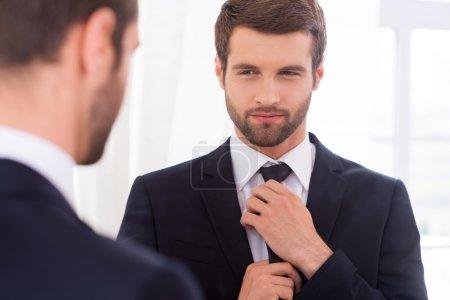 Man in formal wear adjusting his necktie