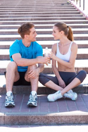 Couple in sports clothing sitting on stairs
