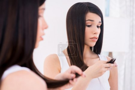 Woman examining her damaged hair.