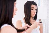 Woman examining her damaged hair.