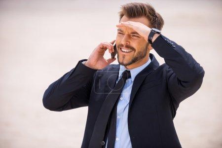 Man in formal wear talking on phone in desert