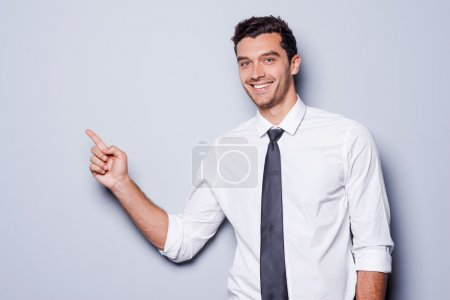 Photo for Businessman pointing copy space. Happy young man in shirt and tie looking at camera and smiling while standing against grey background and pointing copy space - Royalty Free Image