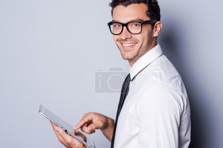 Man in shirt and tie working on digital tablet