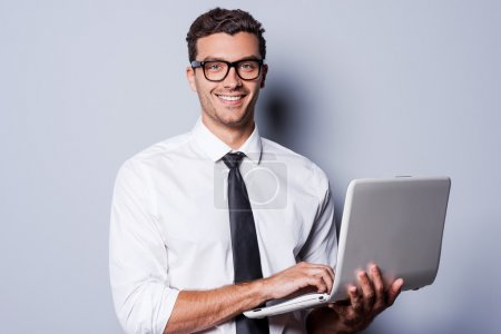 Photo for Confident IT expert. Handsome young man in shirt and tie working on laptop and smiling while standing against grey background - Royalty Free Image