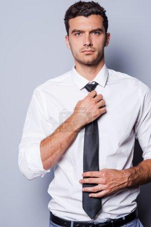 Photo pour Beau et sûr de lui. beau jeune homme en vetu ajuster sa cravate et en regardant la caméra tout en se tenant sur fond gris - image libre de droit