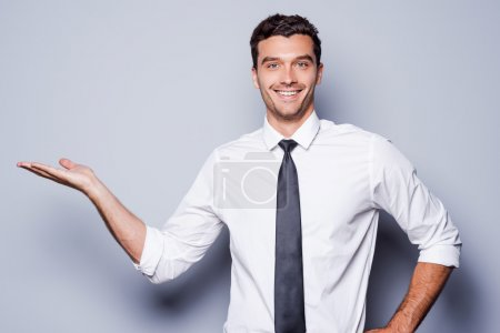 Photo for Copy space on his hand. Handsome young man in shirt and tie holding copy space on his hand and smiling while standing against grey background - Royalty Free Image