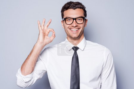 Photo for Everything is OK! Happy young man in shirt and tie gesturing OK sign and smiling while standing against grey background - Royalty Free Image