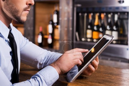 Photo for Surfing web in bar. Close-up of man in shirt and tie working on digital tablet while sitting at the bar counter - Royalty Free Image