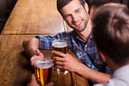 Photo for Friendly talk in bar. Top view of two happy young men talking to each other and gesturing while drinking beer at the bar counter - Royalty Free Image