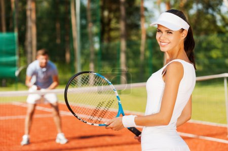 Smiling woman holding tennis racket
