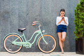 Young woman standing near bicycle