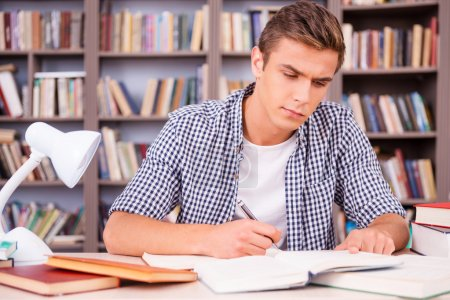 Confident young man making research in library