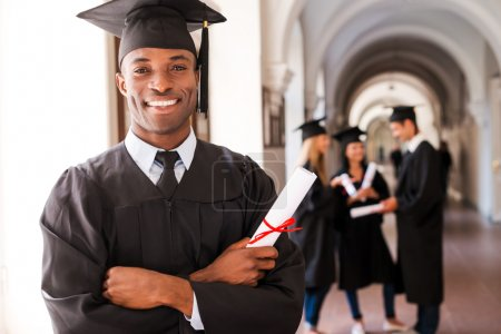 African man in graduation gown holding diploma