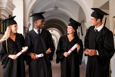 Photo for Talking about bright future. Four college graduates in graduation gowns walking along university corridor and talking - Royalty Free Image