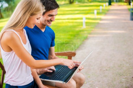 Couple sitting on the bench and looking at laptop