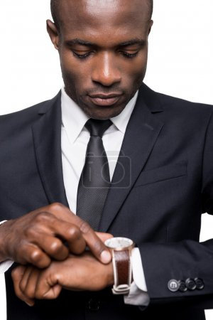 African man in formalwear checking time