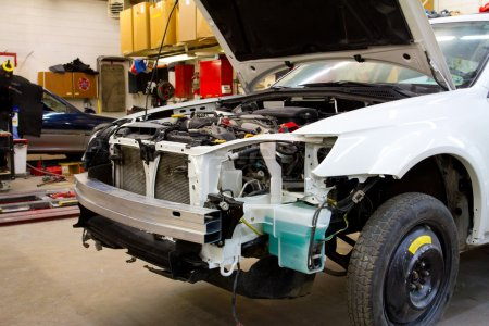 Photo pour Après une collision de grande auto ce véhicule blanc est à l'atelier de réparation automobile pour obtenir fixe au titre de l'assurance. - image libre de droit