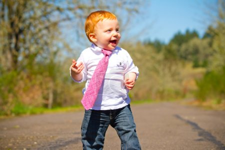 Photo for A one year old boy taking some of his first steps outdoors on a path with selective focus while wearing a nice shirt and a necktie. - Royalty Free Image