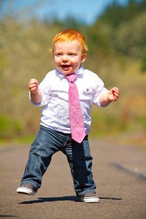 Photo pour Un garçon d'un an faisant quelques-uns de ses premiers pas à l'extérieur sur un chemin avec une concentration sélective tout en portant une belle chemise et une cravate . - image libre de droit