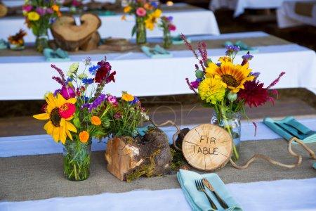 Photo pour Décor de mariage et décorations sont composées de fleurs sauvages et de tronçons transversaux de sapins lors de cette réception naturelle bio en Oregon . - image libre de droit