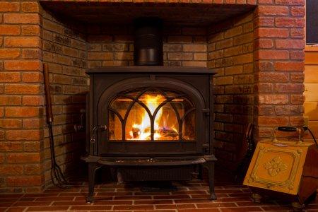 Photo pour Le feu brûle dans une poêle dans une cabane en lodge. - image libre de droit