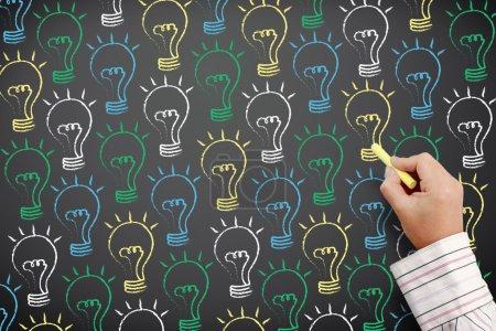 Drawn light bulbs on blackboard