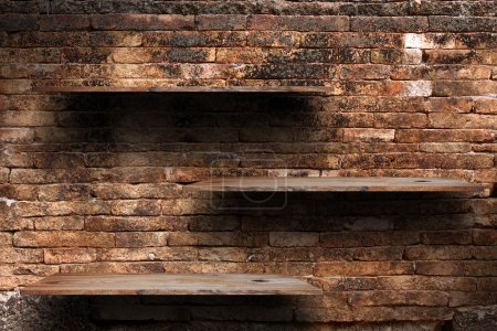 Empty wood shelves on old brick wall background, grunge industrial interior Uneven diffuse lighting version.