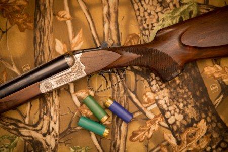 Photo pour Un fusil de chasse rétro en bois avec des cartouches de fusil - image libre de droit
